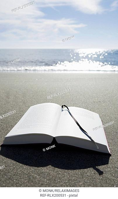Open book on sandy beach, Prunete, Corsica