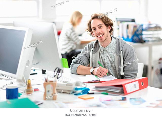 Young man sitting at desk and smiling in creative office, portrait