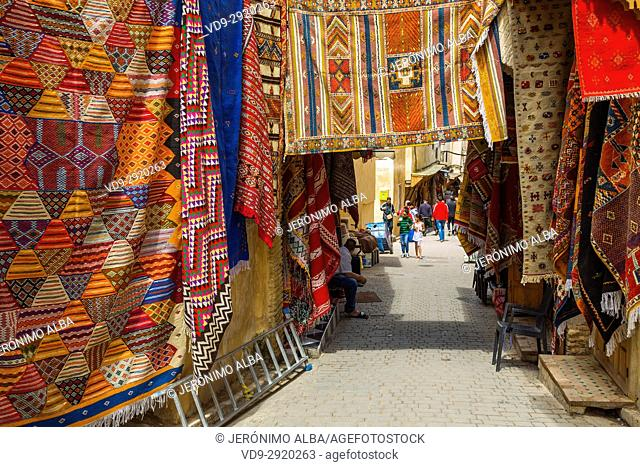 Street life scene. Carpets with traditional patterns for sale at a souq market, bazaar. Souk Medina of Fez, Fes el Bali. Morocco, Maghreb North Africa