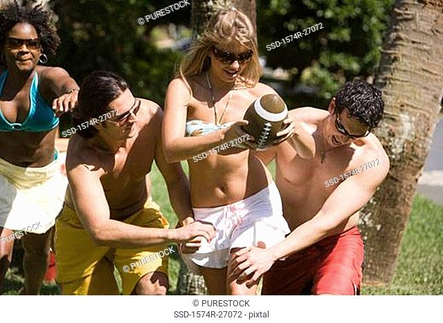 Cheerful friends playing touch football on lawn