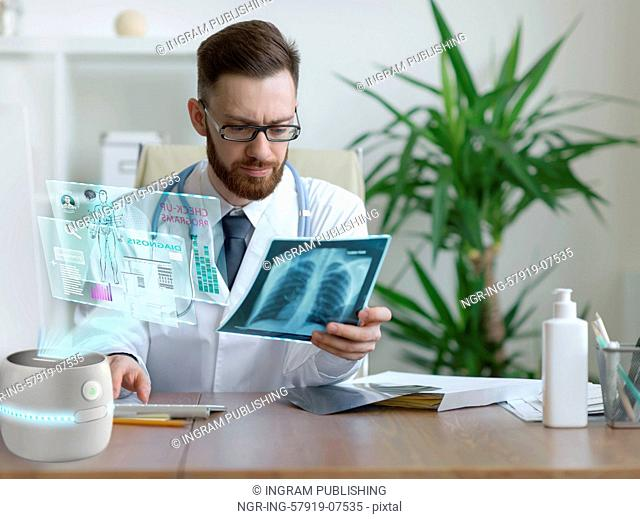 Thoughtful doctor holding chest and lungs xray in medical office