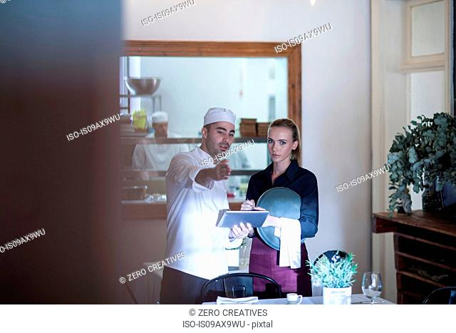 Waitress and chef discussing in restaurant