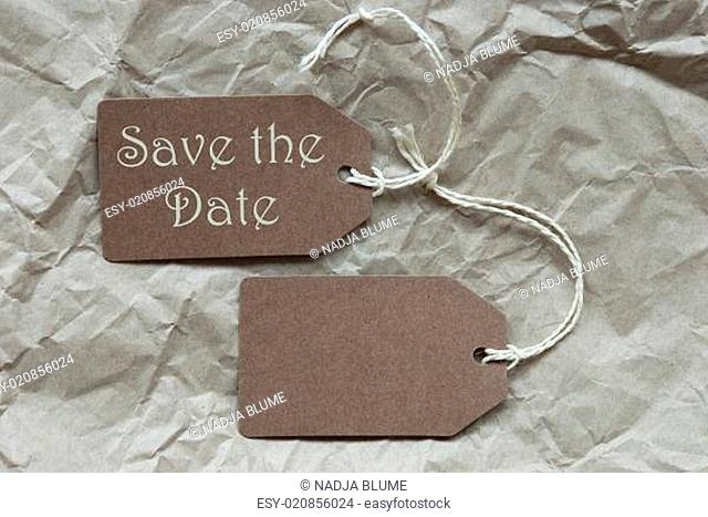Two Brown Labels With Save The Date Paper Background