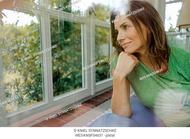 Smiling mature woman on couch at home looking out of window