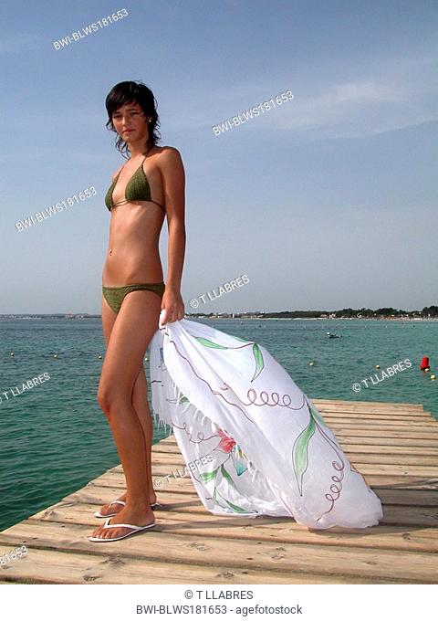 cute young, slim girl in bikini, standing on a boardwalk at the sea with a towel in her hands, Spain, Balearen, Majorca