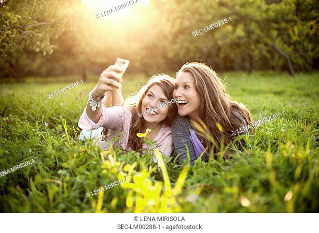 Portrait of two young women lying on meadow and taking picture of themselves