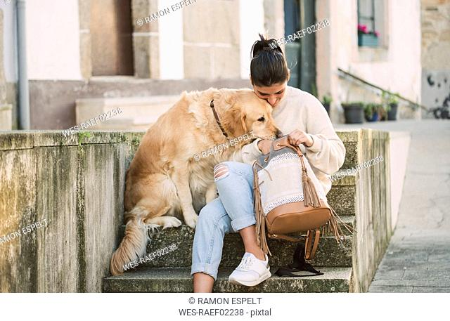 Young woman with her Golden retriever dog on stairs looking in backpack