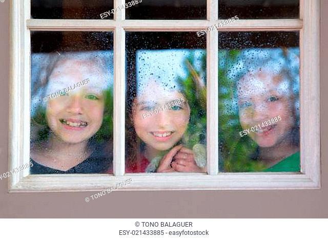 three sister friends looking through the rainy window