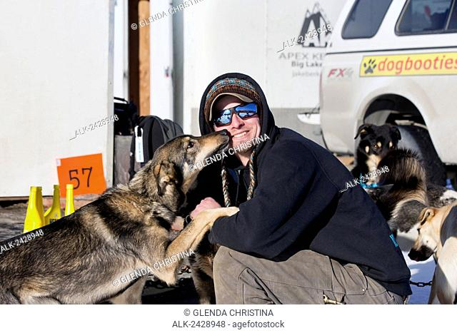 Matt Failor #57 gets some love and kisses from one of his dogs before the 2014 Iditarod restart in Willow, Alaska
