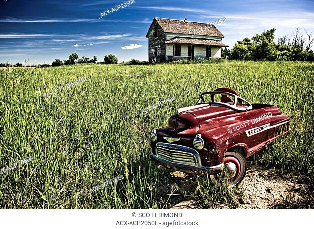 Child's pedal car and abandoned homestead near Camrose, Alberta, Canada