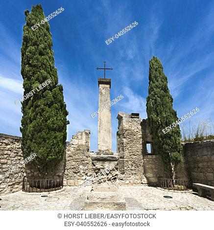 Cross between two cypress trees in Baux-de-Provence. Bouches du Rhone, Provence, France, Europe