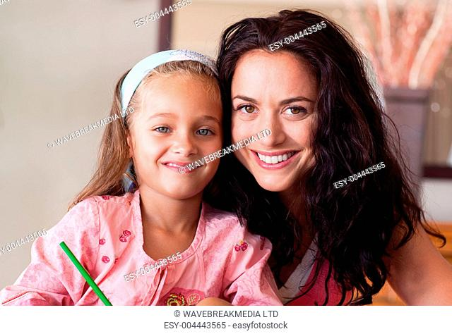 Happy mother helping her daughter for homework