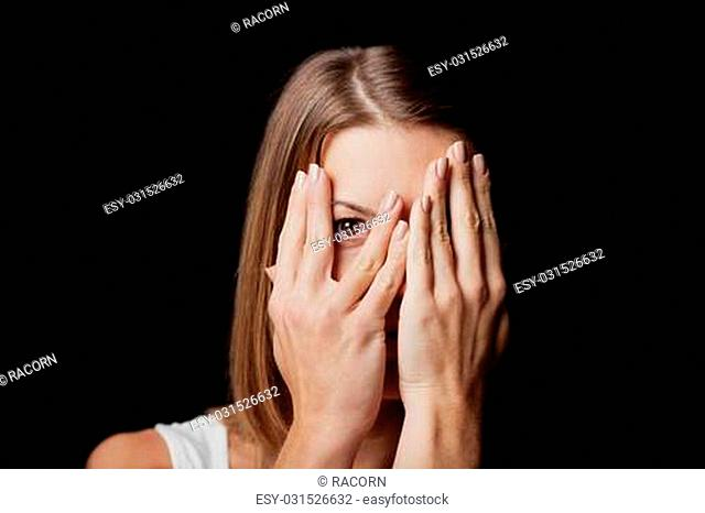 Anxiety - a conceptual image of a woman covering her face with her hands and peering out with one eye between her fingers on a dark studio background