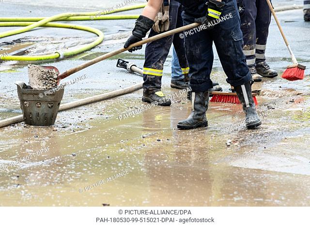 30 May 2018, Germany, Bad Gandersheim: Firemen cleaning the street. The floods which occured after heavy rain on Tuesday evening in the south-Saxon town of Bad...