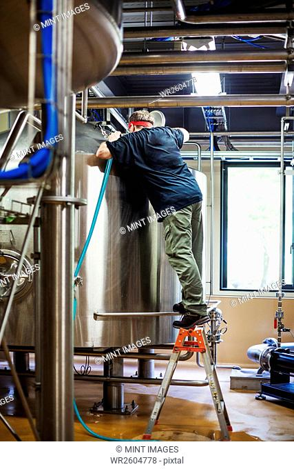 Man working in a brewery adjusting and checking the machinery which transfers the brewed beer around the processing plant