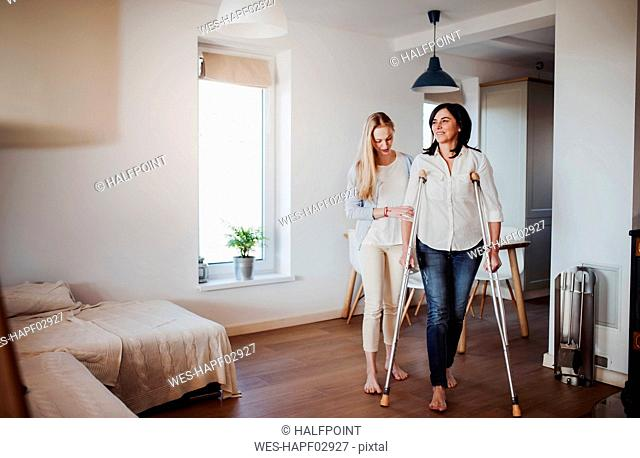 Daughter helping her mother to walk with crutches
