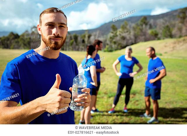Fit man showing thumbs up while holding water bottle