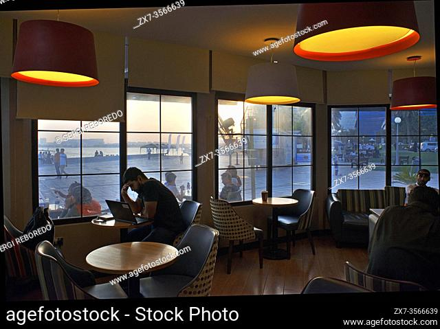 Inside Costa coffee restaurant and modern skyline of the West Bay central financial district, Corniche promenade at Sheraton park Doha, Qatar, Middle East