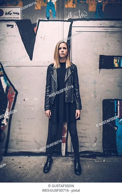 Portrait of serious young woman dressed in black standing in front of graffiti