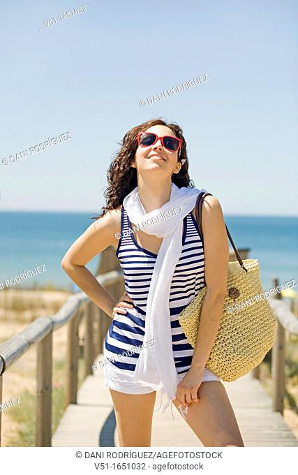 Woman arriving at the beach and smiling at camera
