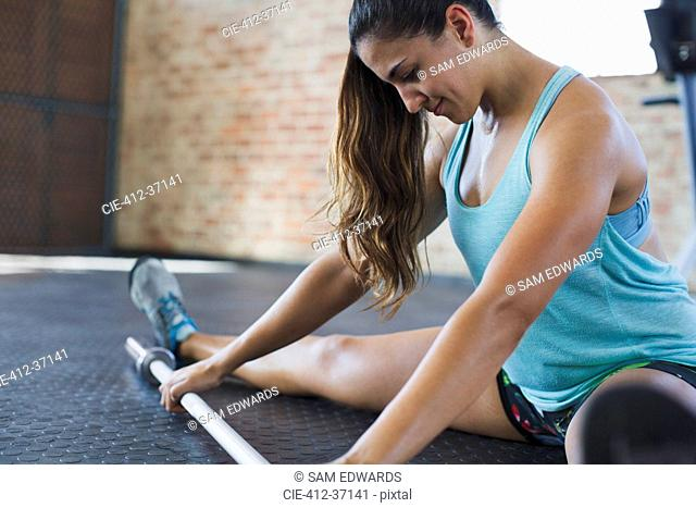 Focused young woman stretching leg, using barbell in gym