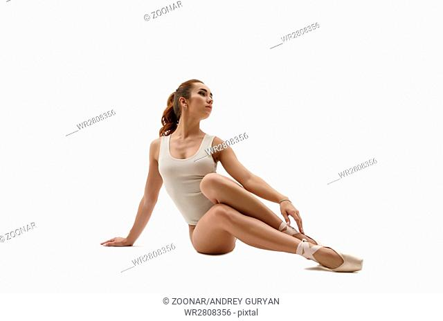 Beautiful ballet dancer sitting. Isolated on white