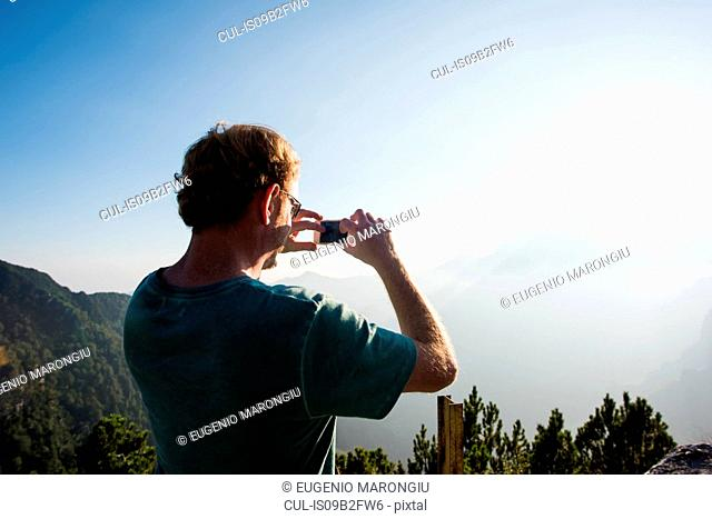 Rear view of man taking photograph of mountains, Passo Maniva, Italy