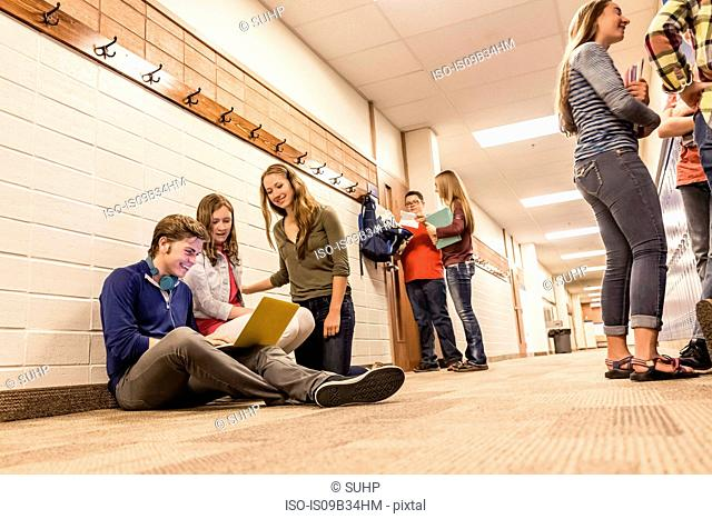 Teenagers looking at laptop in high school corridor