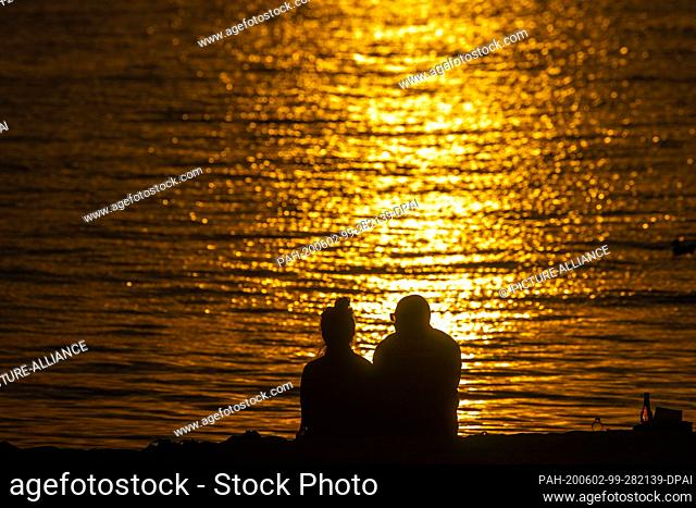 02 June 2020, Mecklenburg-Western Pomerania, Timmendorf (poel): Holidaymakers sit on the beach on the island of Poel and watch the sunset