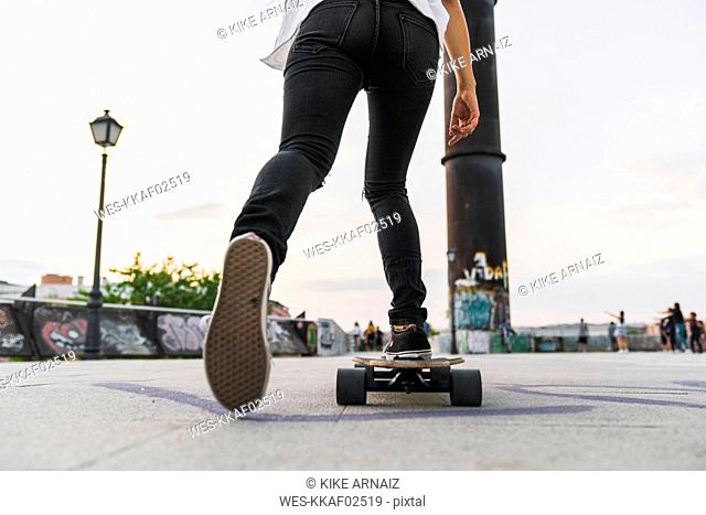Close-up of young woman riding skateboard in the city