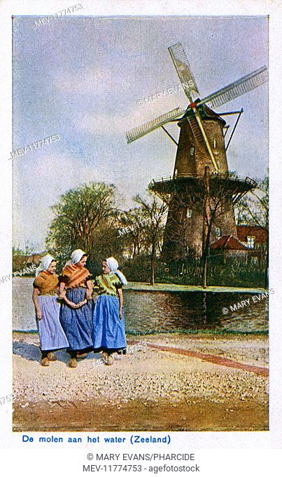 Three local girls in traditional costume, and a windmill with a platform, Zeeland, Netherlands