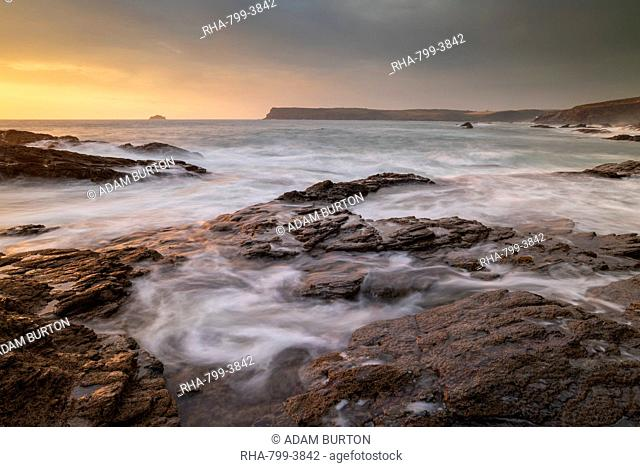 Waves swirl over rocky ledges at sunset on the North Cornwall coast, Cornwall, England, United Kingdom, Europe