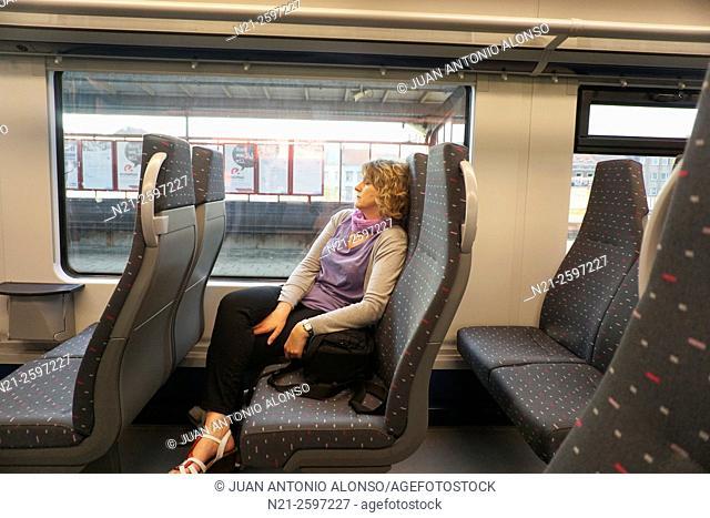 Woman sleeping on the Antwerp-Brussels train. Belgium, Europe