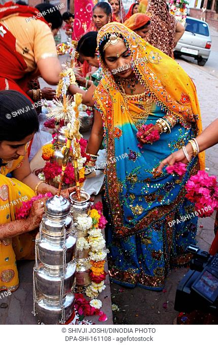 Rajasthani Marwari women preparing silver lotiyan or metal pots on occasion of Gangaur ; Jodhpur ; Rajasthan ; India NO MR