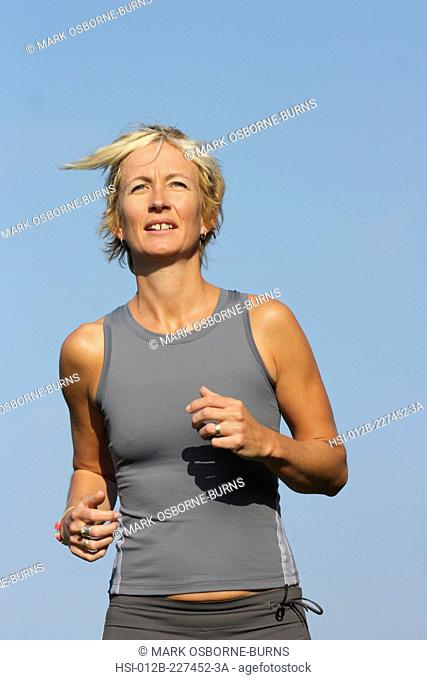 Blonde woman outdoors. Close-up. Jogging in countryside
