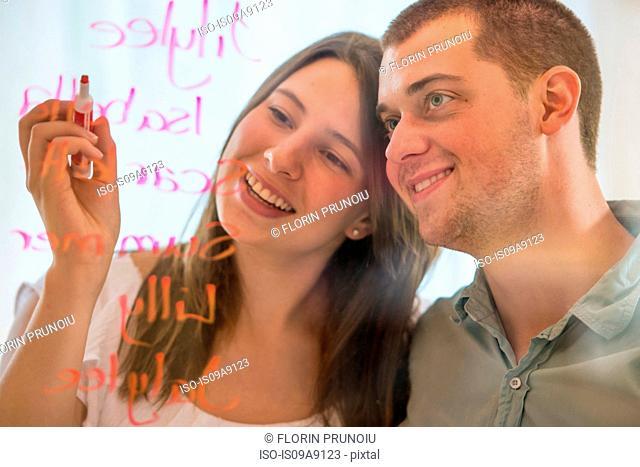 Couple writing list of names on glass