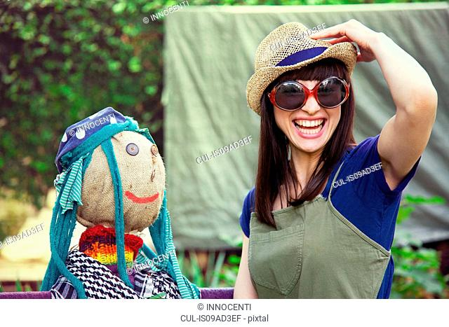 Woman wearing sunglasses and hat with scarecrow