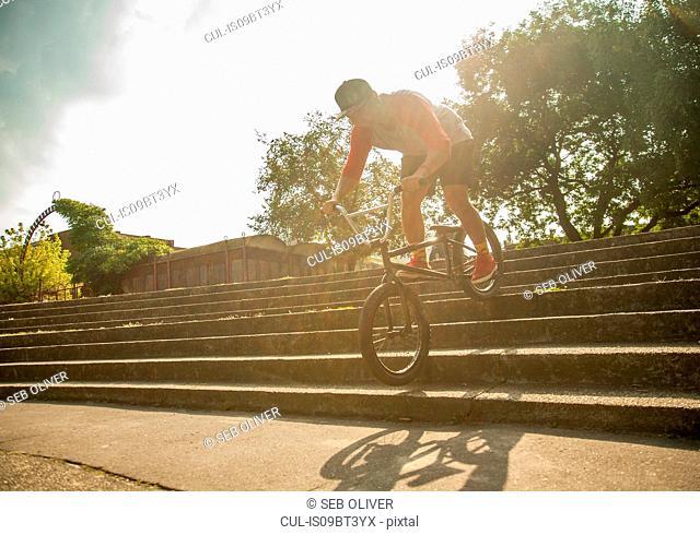BMX cyclist doing stunt on steps