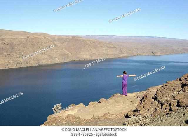 A young girl on a cliff stretching her arms near the Columbia River at a scenic outlook near Ellensburg, Washington, United States