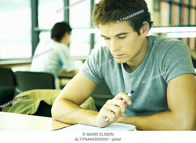 Male college student sitting in library, studying
