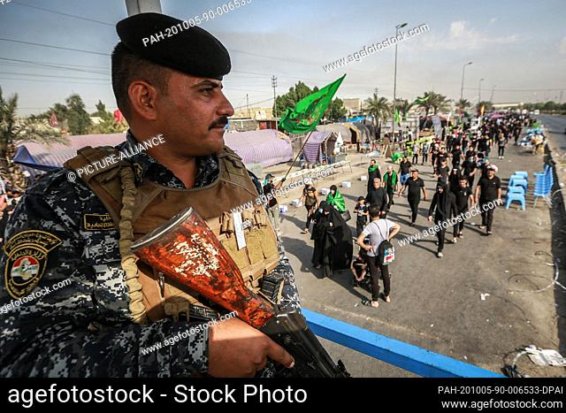 05 October 2020, Iraq, Karbala: A member of the Iraqi security forces observes Shia Muslims march from Baghdad to visit the the Husayn Mosque in Karbala on the...