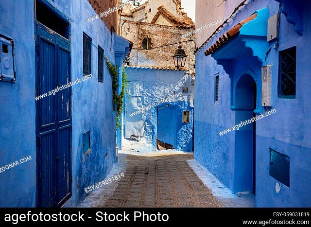 Narrow streets and blue painted houses of Chefchaouen city, Morocco. Most of the streets full of handmade colorful crafts