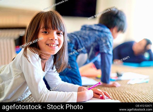 Portrait happy girl coloring on floor