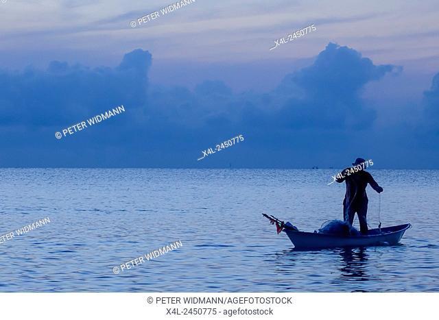 Sunrise, fisherman in his boat on the sea, Sai Keaw beach in Nakhon Si Thammarat, Thailand, Asia