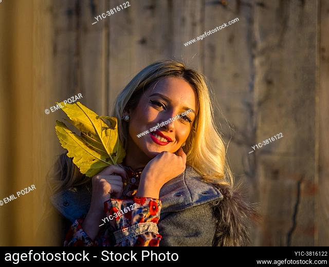Young woman is holding big Yellow-Green Autumnal leaf in hand looking at camera