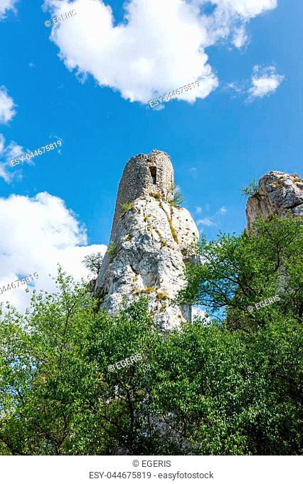 White rock in forest, national park, green trees, blue sky with clouds