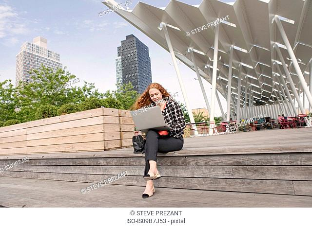 Young businesswoman sitting outside hotel using laptop, New York, USA