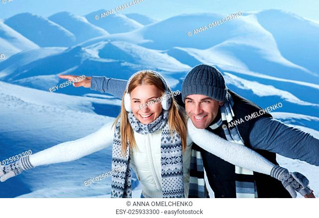 Happy couple playing outdoors in winter, imitate the flight by hands, having fun together in the snowy mountains, with pleasure spending Christmas holidays