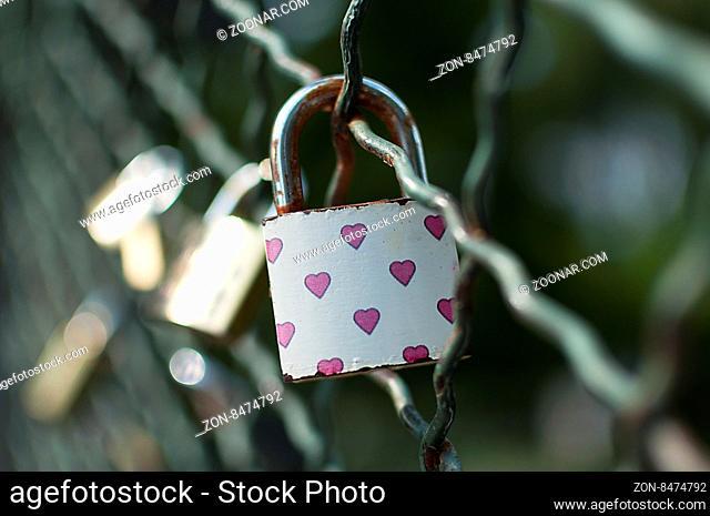 Close-up on lockers symbolizing everlasting love on a bridge fence