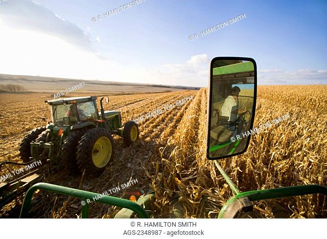 Agriculture - View of grain corn harvest from the cab of a combine, showing a tractor alongside pulling a grain cart and the combine operator reflected in the...